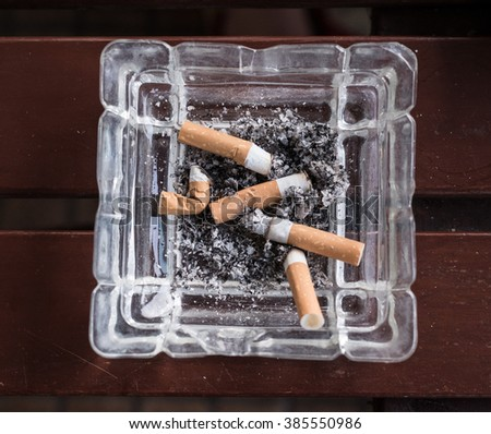 cigarette stub with ashes in the ashtray. Smoke and cancer.  - stock photo