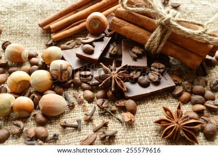 cinnamon, chocolate, coffee, cloves, hazelnuts walnuts on sacking background - stock photo