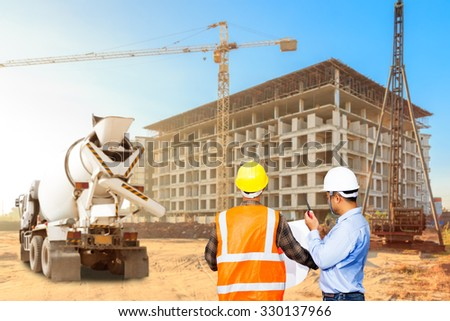 Civil engineer and foreman control working at a construction high building area