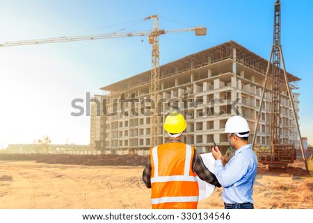 Civil engineer and foreman control working at a construction high building site