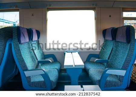 2 class seats in the modern european train with white isolated window - stock photo
