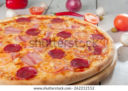 Close up Delicious Meat Pizza with Salami, Bacon and Tomato Slices on a cutting board on white wooden background with different colourful vegetables top view - stock photo