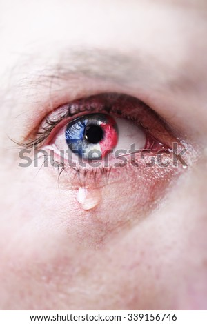 Close up eye of young man crying sad in tears with french flag reflection on his iris - stock photo