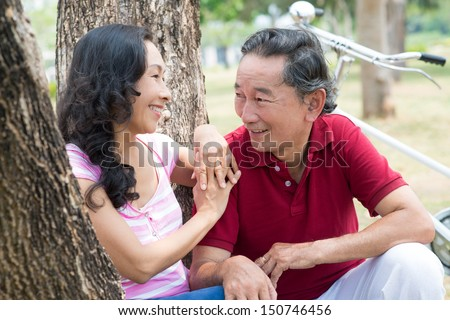 Close-up image of seniors talking after riding bicycles in the park on the foreground  - stock photo