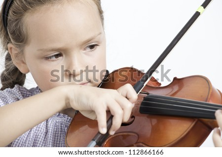 Close  up of a child playing violin on isolated white background - stock photo