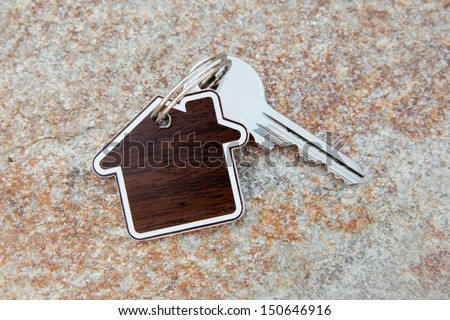 close up of house shaped keychain and key - stock photo
