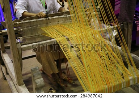 Close up of old woman weaving blue and white pattern on loom - stock photo