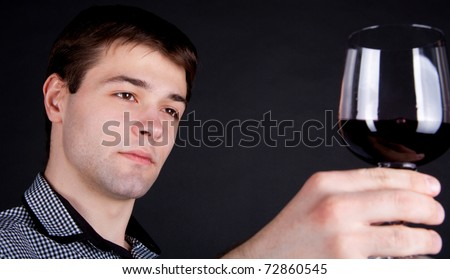 close-up of young Man evaluating the quality   of red wine - stock photo
