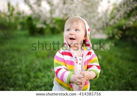 close-up portrait of a beautiful baby girl sweet happy on a background of green grass in the park lifestyle smiling in a white tunic and trousers