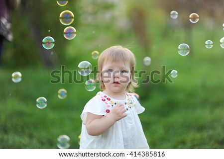 close-up portrait of a beautiful baby girl sweet happy on a background of green grass in the park lifestyle smiling in a white tunic and trousers   in soap bubbles