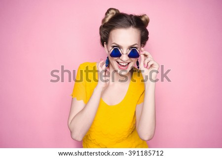 close-up portrait of a beautiful young hipster lifestyle slim blond girl in fashionable sunglasses on a pink background in the studio in a yellow  T-shirt  smiling and posing