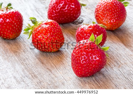 Close-up view of red strawberry on wooden floor - stock photo