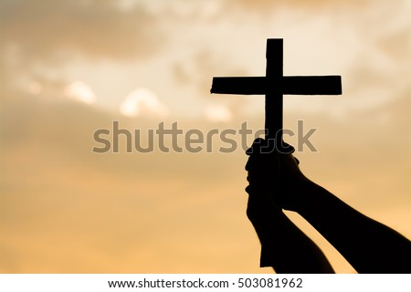 Close up woman hand holding wood cross or religion symbol shape over a sunset sky with clouds background for Gods,Christianity, religious, faith, holy, spiritual, Jesus, belief or resurrection.