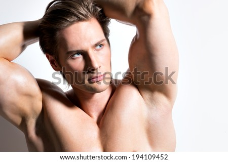 Closeup portrait of a handsome sexy muscular man posing on a white background with contrast shadows. - stock photo