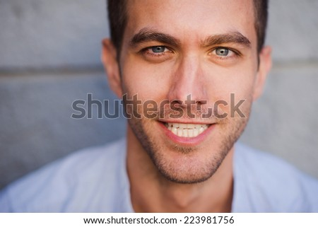 closeup portrait of a handsome young man smiling outside  - stock photo