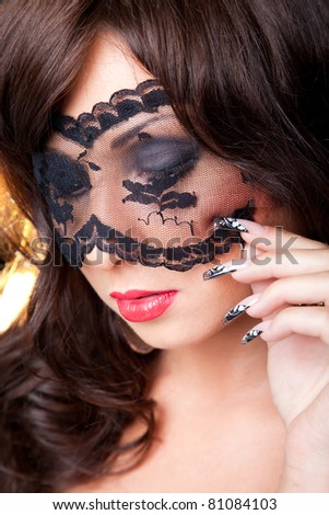 Closeup portrait of attractive young brunette girl with long dark ringlets and fine art manicure wearing lacy mask on her eyes - stock photo