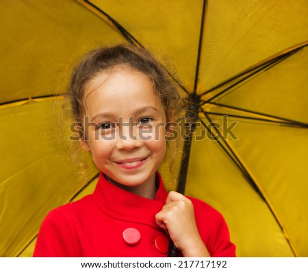 closeup portrait of cute curly school girl holding a yellow umbrella