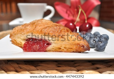 Closeup shot of French pastry, cherry turnover, with cherries and blueberries on the side.White cup and red lily flower in the background. - stock photo