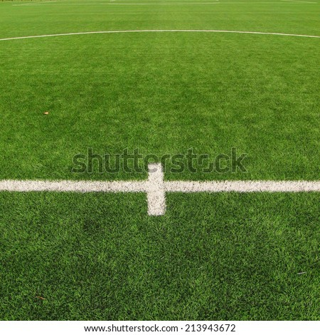 Closeup view to white lines on artificial grass field on football playground. Detail of a cross of lines in a soccer field. Plastic grass and finely ground black rubber. - stock photo