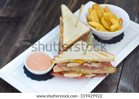 Club sandwich on toasted, served with crispy golden potato French fries