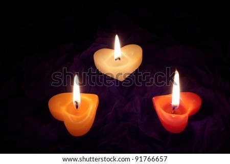 Co loured candle shaped heart on black backcloth