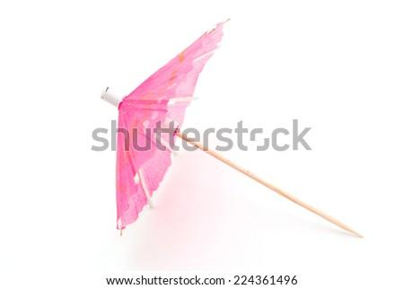 Cocktail decoration, pink umbrella on white background - stock photo