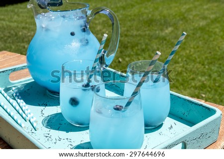 3 cocktail glasses and pitcher filled with blueberry lemonade with flavored vodka sitting in blue drink tray on wood table - stock photo