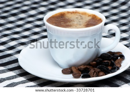 Coffee cup close-up over dark roasted coffee beans