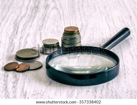 coins and magnifying glass on a light background, close-up, vintage, retro style - stock photo