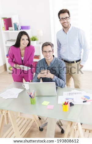3 colleagues talking about a project in front a computer - stock photo