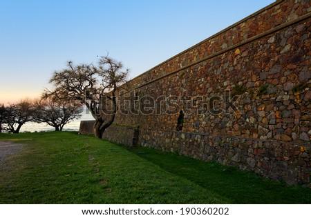 Colonia del Sacramento, Uruguay. The historic quarter is an UNESCO World Heritage Site. Fortress Wall enlighten by the sunrise. - stock photo