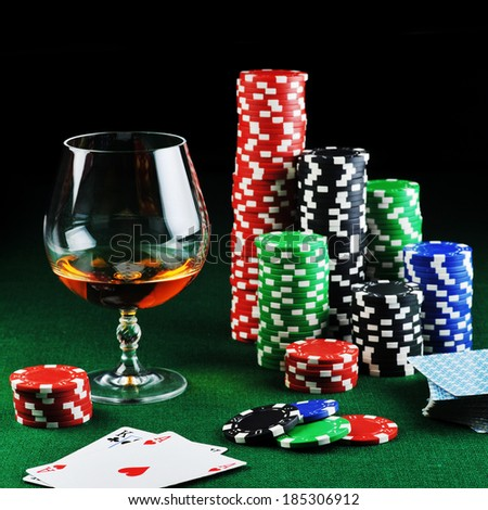 color chips for gamblings, drink and playing cards on green - stock photo