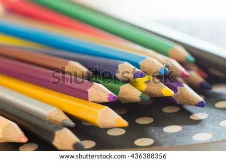color pencils and notebook on wooden table