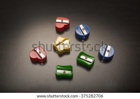 Colored pencil sharpeners/Colored Pencil Sharpers/Various colored pencil sharpeners on a plain surface - stock photo