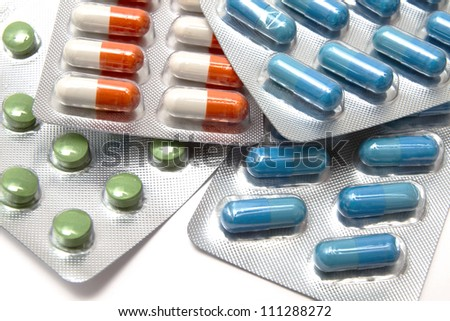 colorful capsules and pills closeup on white - stock photo
