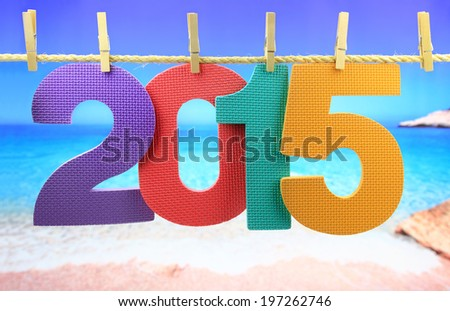 Colorful number 2015 year hanging on a rope in front of the sea - stock photo