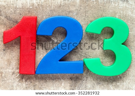 123 colorful plastic number on the canvas background - stock photo