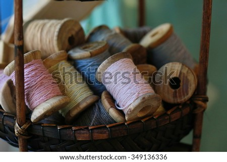 colorful silk thread roll in basket - stock photo