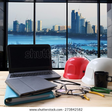 computer and builder's work tool on wooden table with cranes at the container port terminal with big city background - stock photo