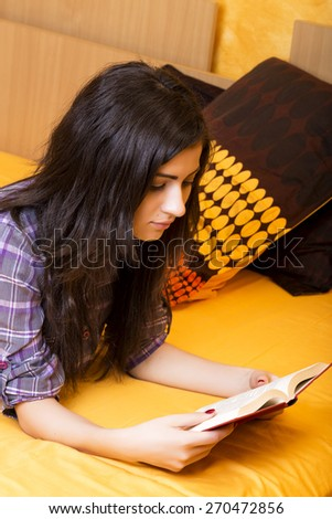 Concentrated teenage girl reading a  book on the bed in her room - stock photo