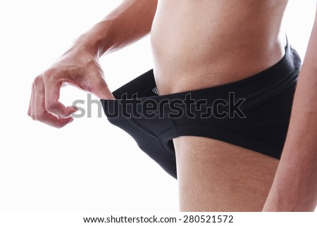 Concept photo of male sexuality and problems. Man pulling his black underwear. - stock photo
