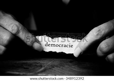 Concept  woman with message on paper in hands - democracie ( democracy in french) - stock photo