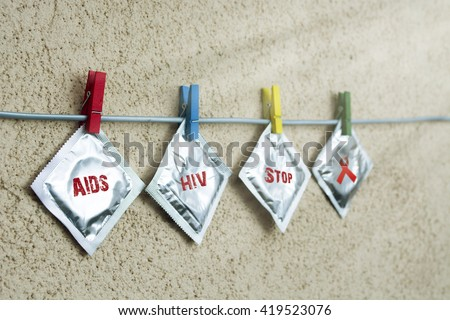condom and sealed condoms on colorful clothespins. aids  ribbon symbolic concept. help campaign on people  support on HIV STD heart disease. World Remembrance Day of AIDS Victims. sun filter - stock photo