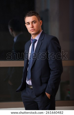 Confident modern businessman keeping his hands in trousers pockets. Shot in room - stock photo