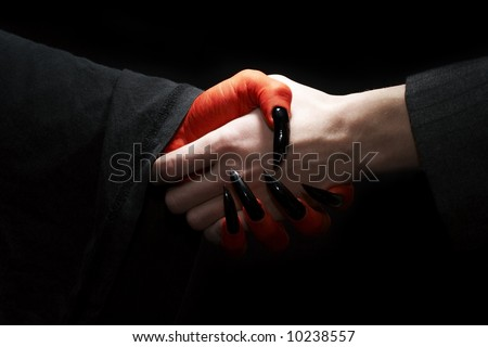 ?conomic conceptual image. Male businessman handshake with devil. Dark contrast lighting - stock photo