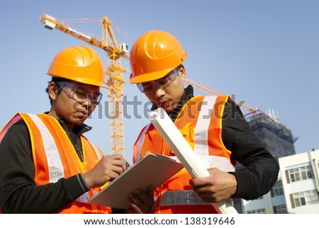 construction engineer with safety vest discussion under construction