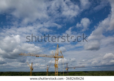 Construction tower cranes against a blue sky with the horizon