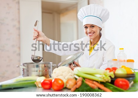 cook in white uniform tests  soup with ladle at commercial kitchen   - stock photo