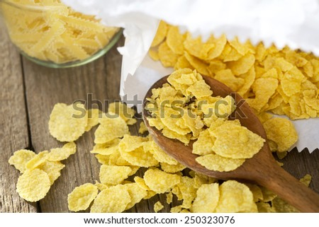 cornflakes on wooden table - stock photo