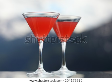 Cosmopolitan cocktail made with vodka, triple sec, cranberry juice, and freshly squeezed lime juice, mountains on the background - stock photo